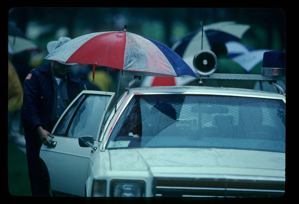 Policemen protecting themselves against the rain as they exit their squad car during the 1982 Masters