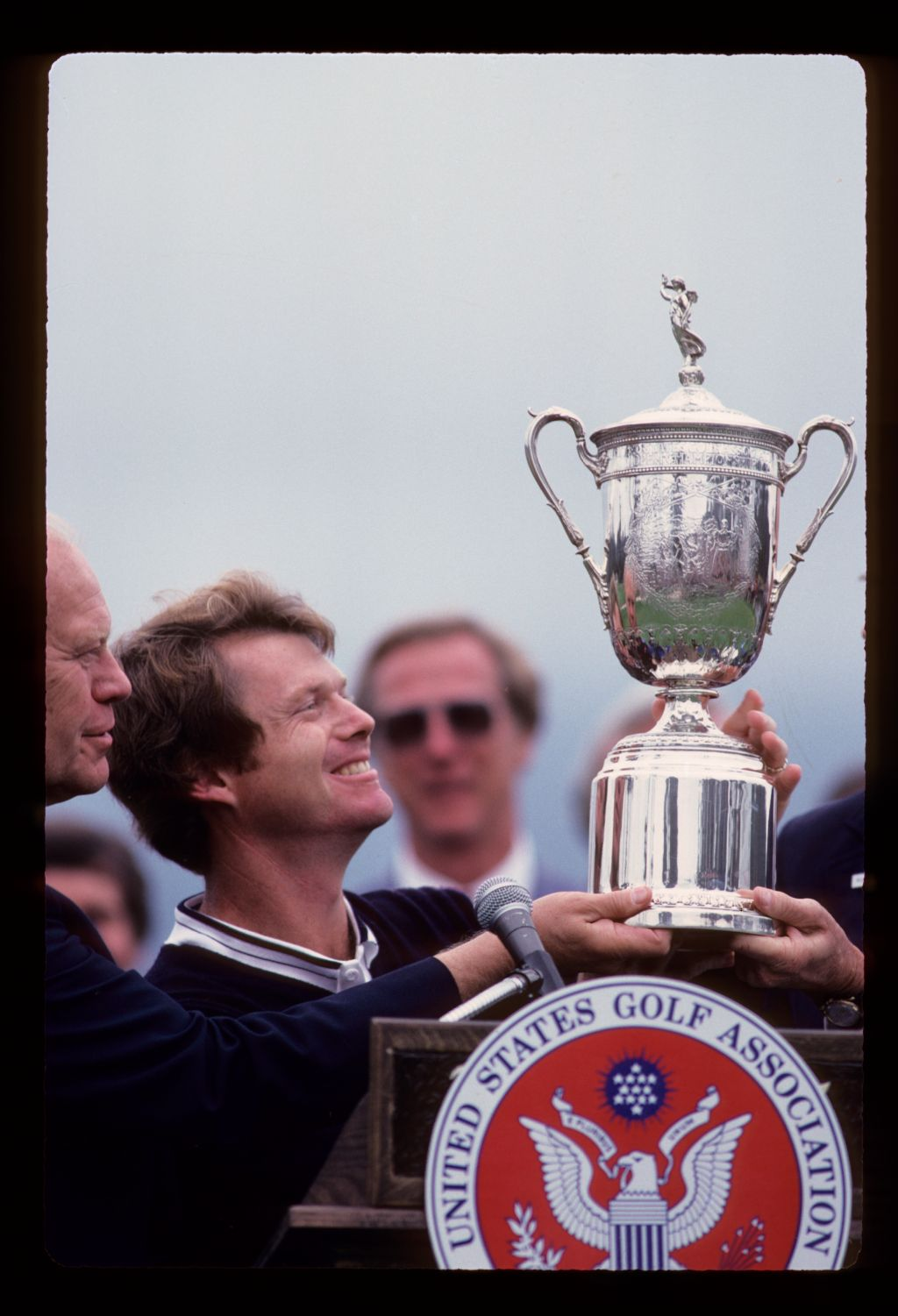 A victorious Tom Watson admires the US Open trophy while President Gerald Ford looks on