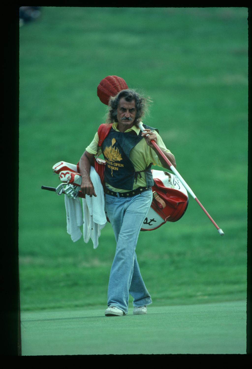 The caddie, Alex. tends the wicker basket as the pin flag at the 1981 U. S. Open Championship at Merion
