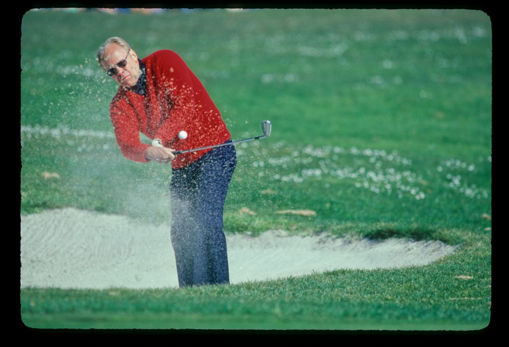 President Gerald Ford splashes out of the greenside bunker at the Bing Crosby Pro-Am Golf Championship