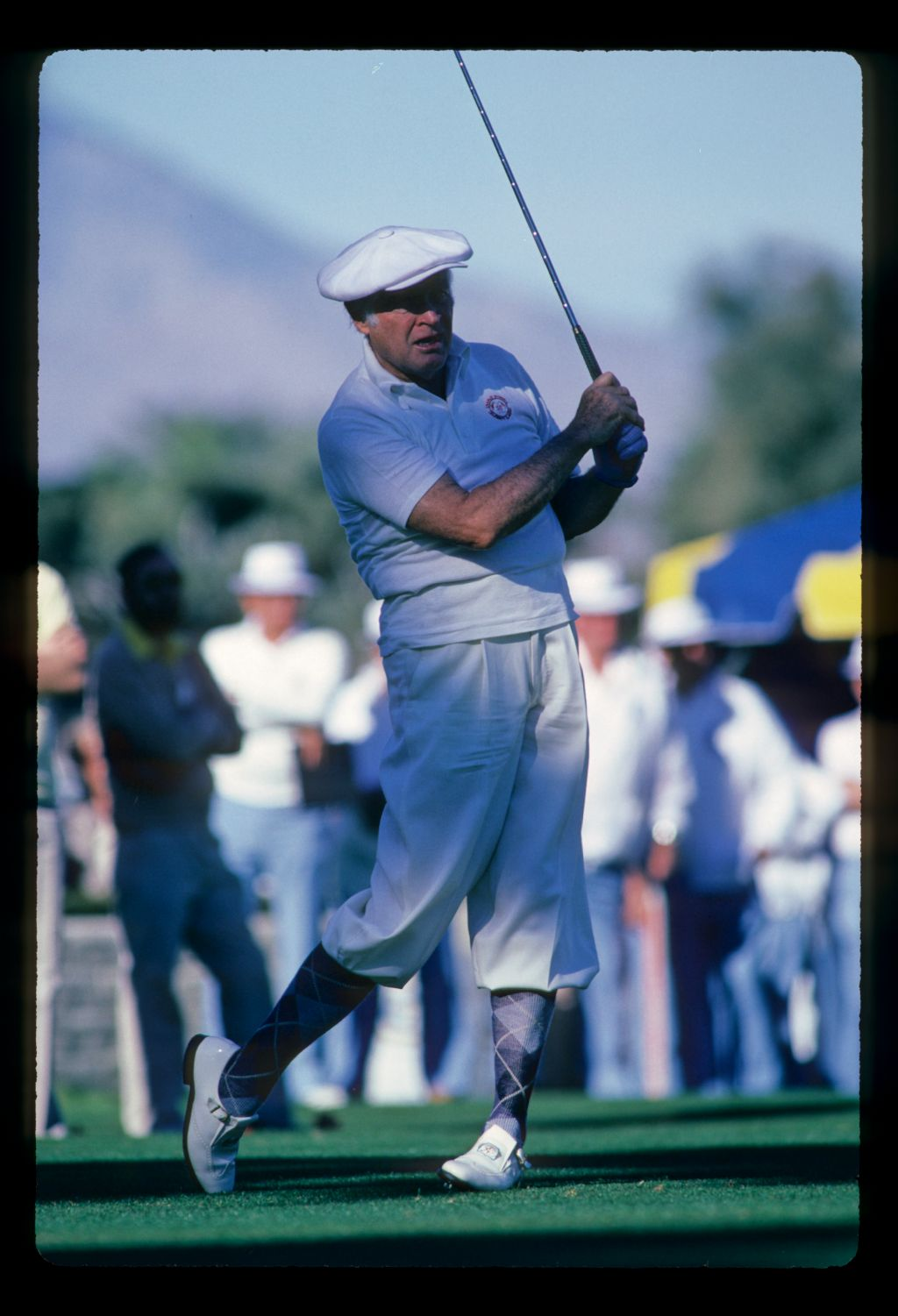 Actor Bob Hope watches his tee shot closely at the Bob Hope Desert Classic Golf Tournament