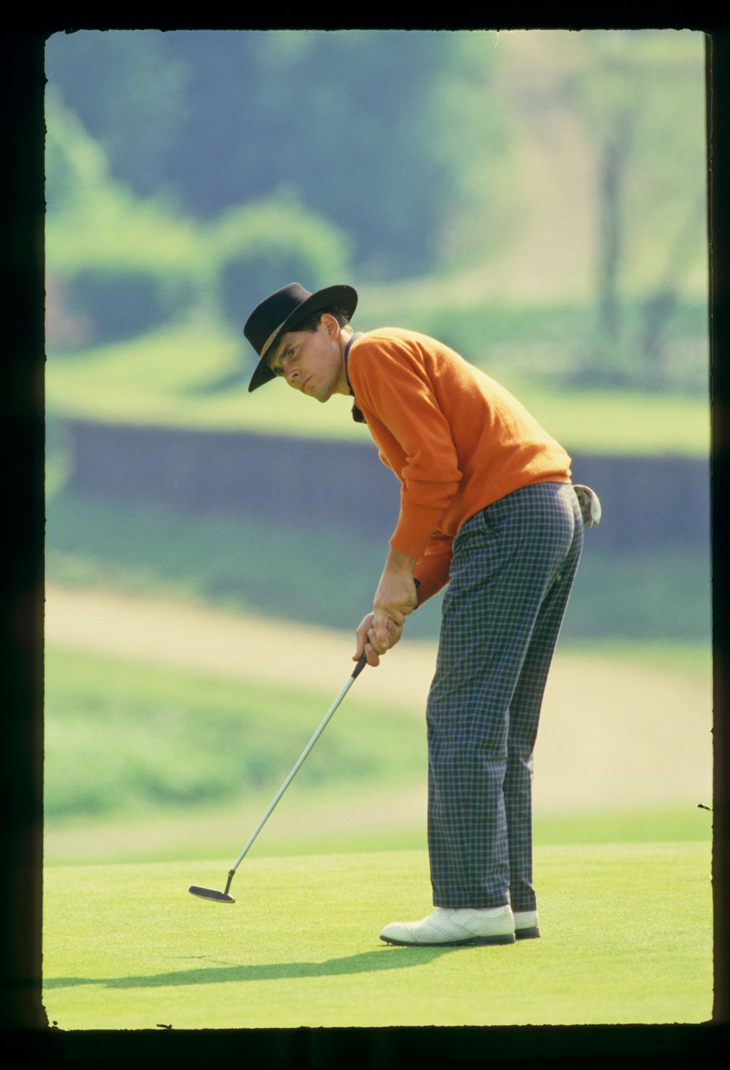 English golfer Robert Lee, in Stetson hat, sending a putt on its way at the 1987 Epson Grand Prix