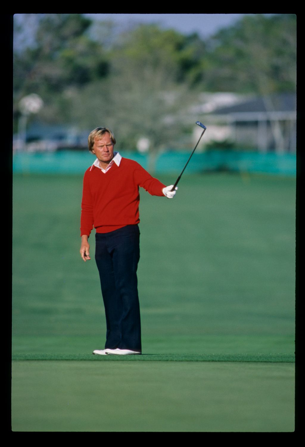 Jack Nicklaus pointing his putter at the hole while putting from the fringe during the 1983 Bay Hill Classic