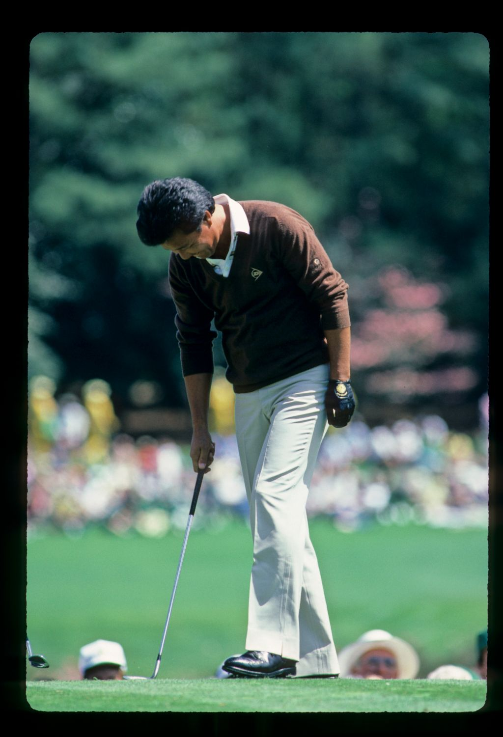 Isao Aoki knocking down his divot after hitting wedge from the tee during the 1984 Masters