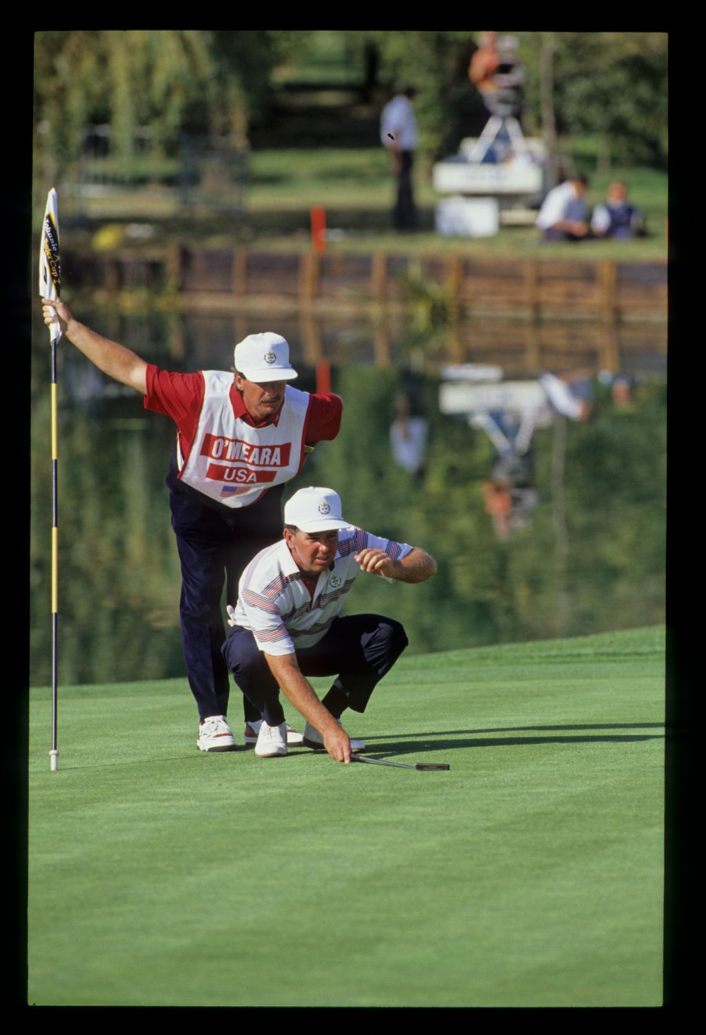Mark Mc Cumber lining up his putt as his caddie stands behind him on the tenth green in front of a mirror calm lake at the 1989 Ryder Cup