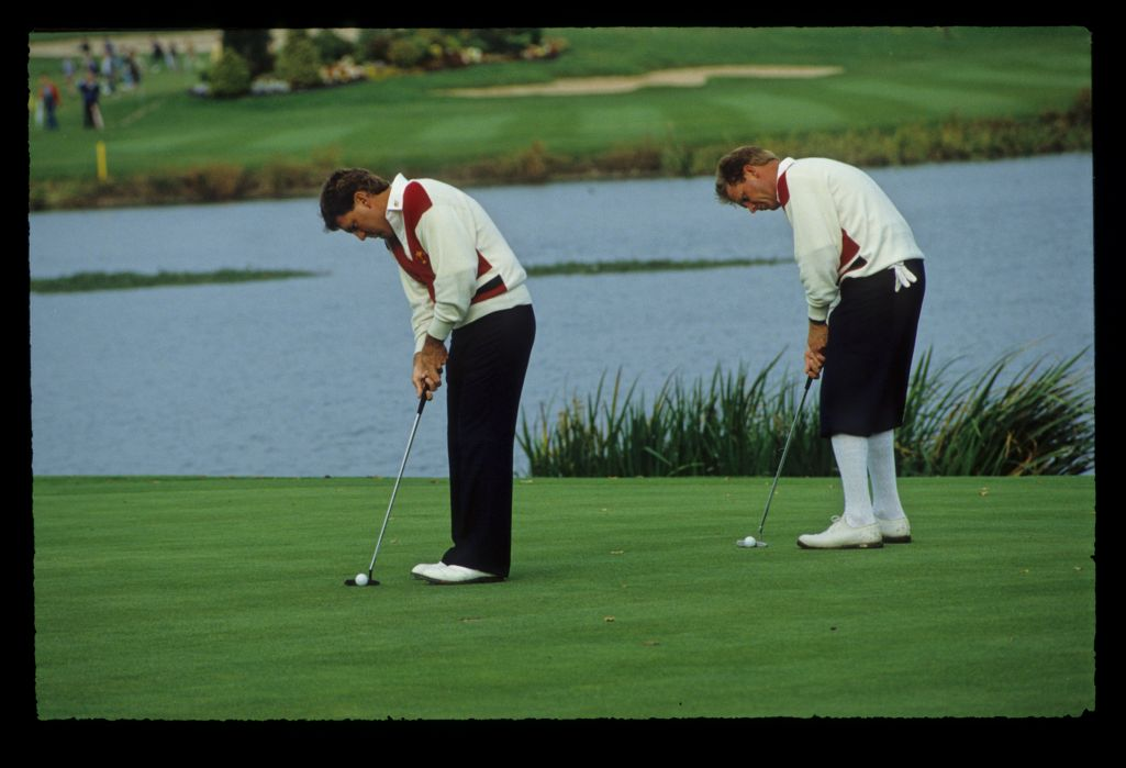 Partners, Lanny Wadkins and Payne Stewart looking like synchronised golfers as they practice putting at the 1989 Ryder Cup