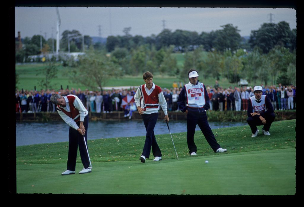 Curtis Strange sending his putt on its way as partner, Paul Azinger walks across to consider his own putt at the 1989 Ryder Cup