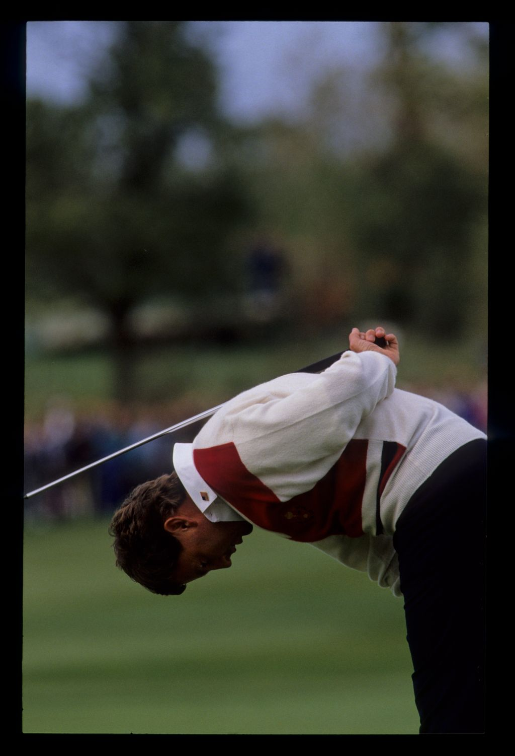 Lanny Wadkins looking as though he is practicing calisthenics after missing a putt at the 1989 Ryder Cup