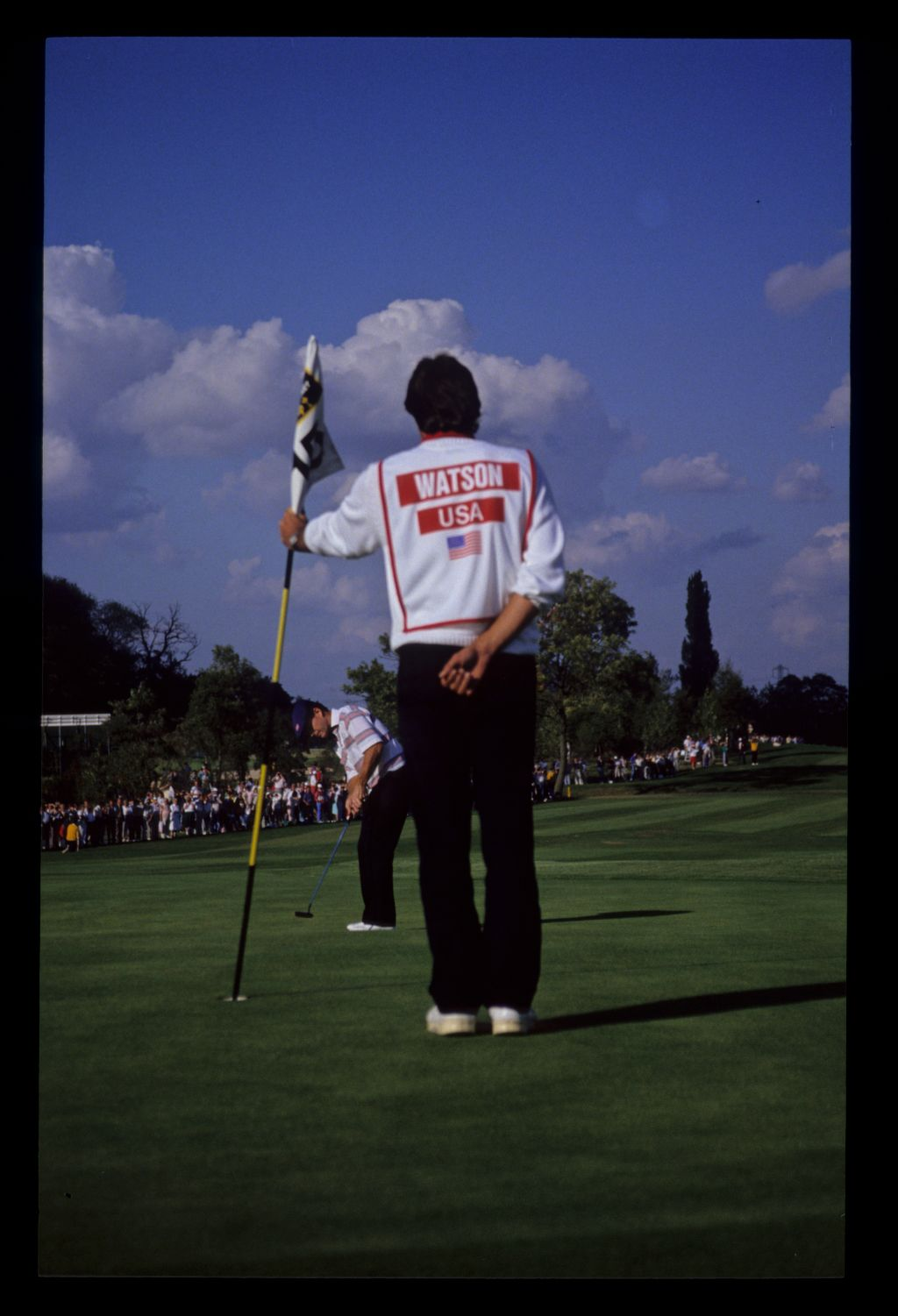 With caddie tending the flag, Tom Watson prepares to putt at the 1989 Ryder Cup