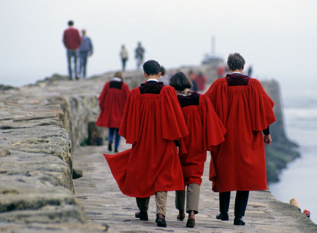 St Andrews University students walking the traditional Pier Walk in their red gowns