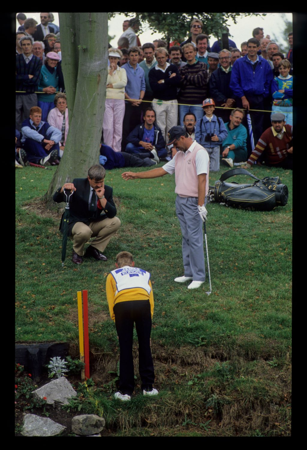 Mark James dropping out of a water hazard as a rules official and his caddie look on at the 1989 Ryder Cup with a banked gallery watching