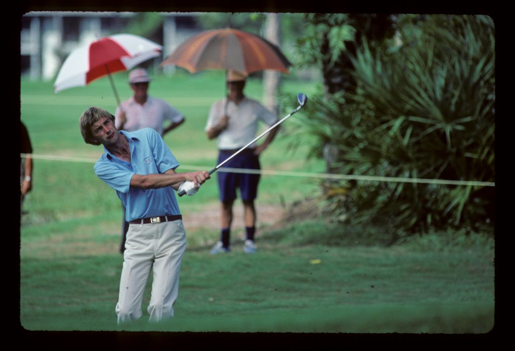 Spectators using umbrellas as sunshades while Ken Brown pitches to the green with a sand wedge at the 1983 Ryder Cup
