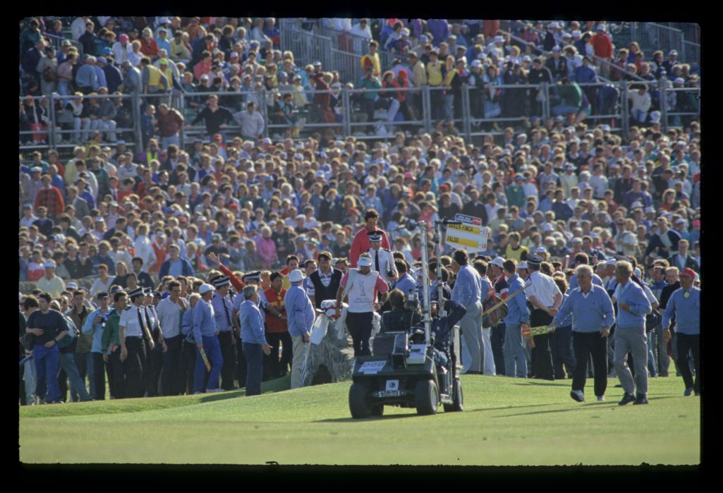 Ian Baker Finch and Nick Faldo crossing the Swilcan Bridge in front of huge crowds during the 1990 Open Championship