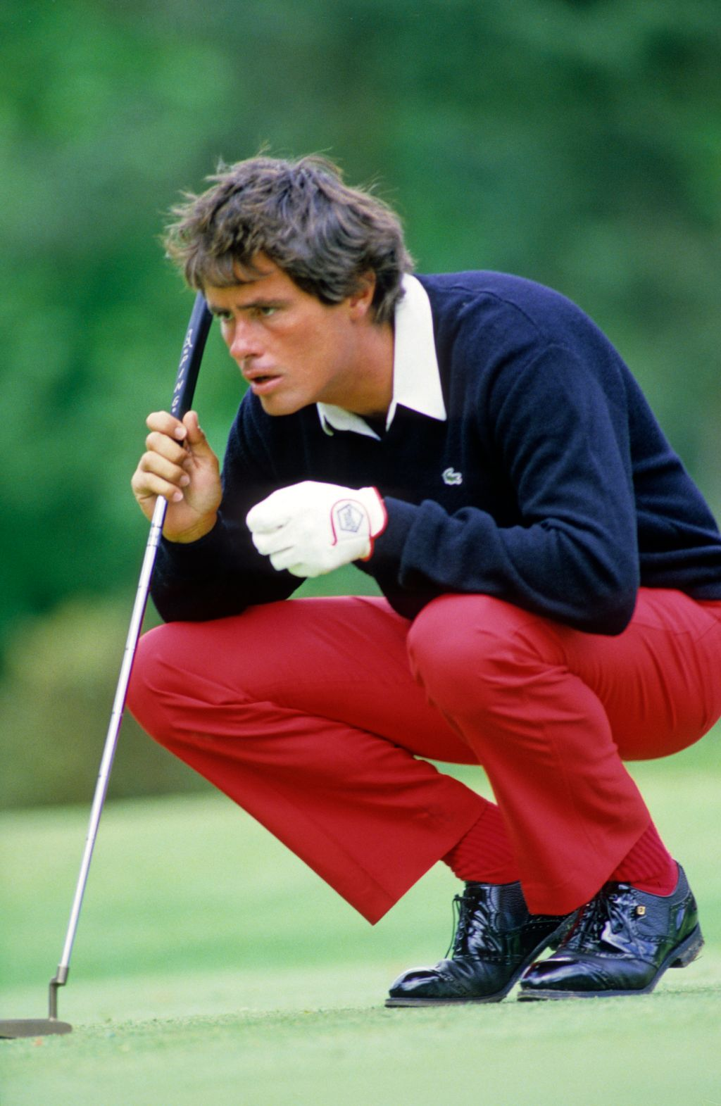 Ian Baker Finch squatting to line up a putt during the 1985 Dunhill British Masters