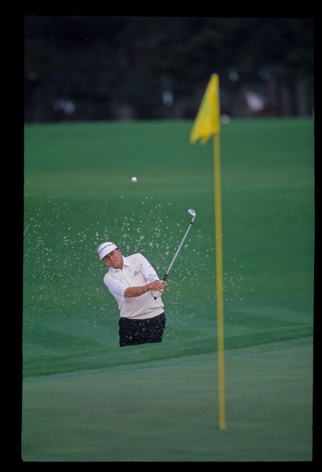 The ball is on its way as Raymond Floyd splashes out of a bunker during the 1992 Masters