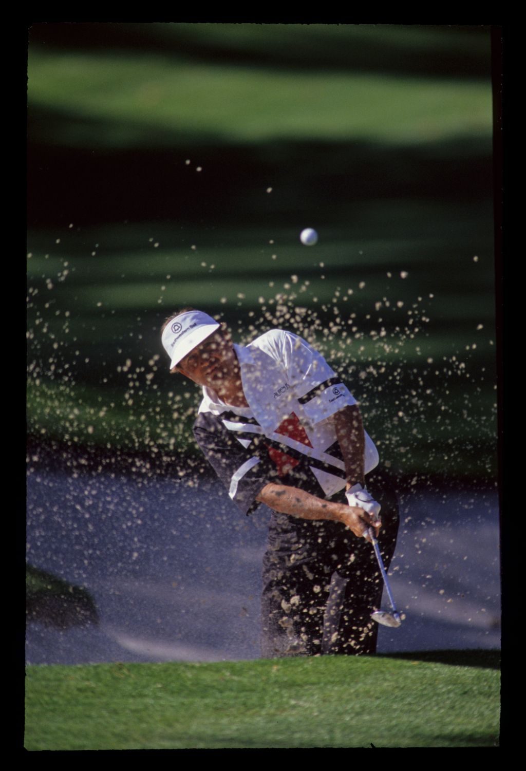 Sand obscures Raymond Floyd as he splashes out of a bunker during the 1990 Masters