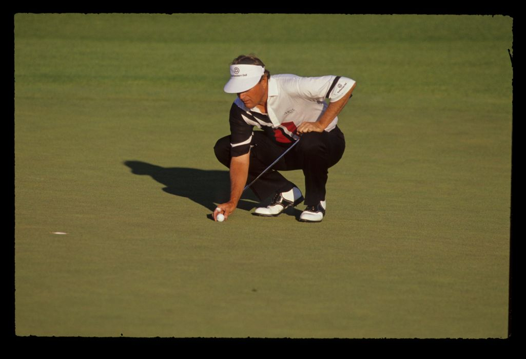 Raymond Floyd keeps his eye on the line of his putt as he replaces his ball on the green during the 1990 Masters