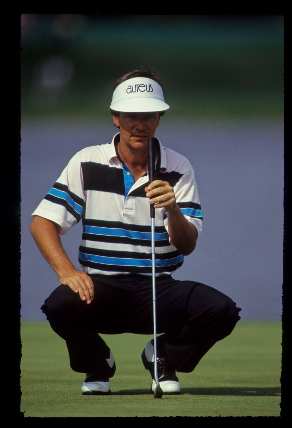 Larry Mize squatting to line up a putt during the 1990 Nestle Invitational