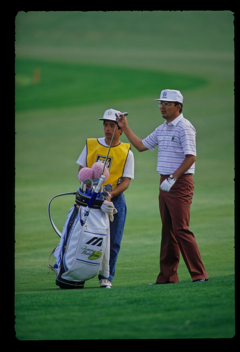 Tommy Nakajima and his caddie considering a shot from the rough on his way to sixth place during the 1987 Hertz Bay Hill Classic