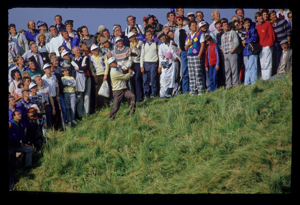 Tommy Nakajima playing from thick rough on a hillside during the 1986 Open Championship