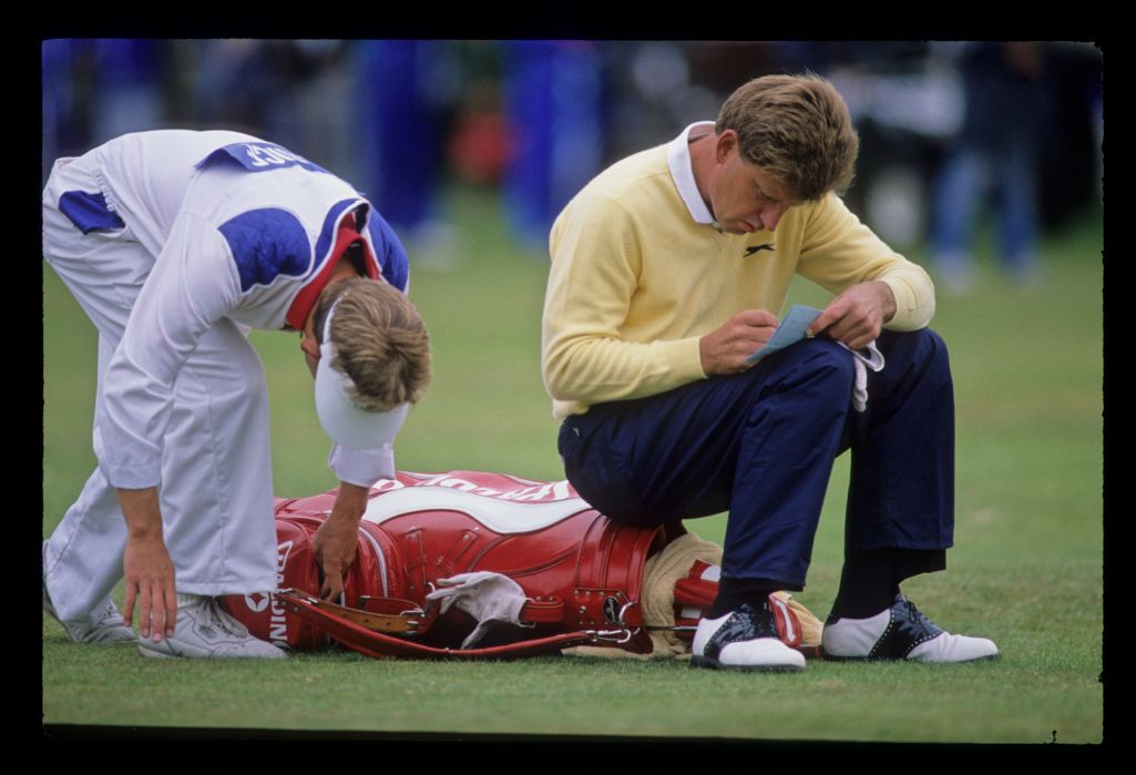 Nick Price sitting on his bag as he marks his card during the 1988 Open Championship