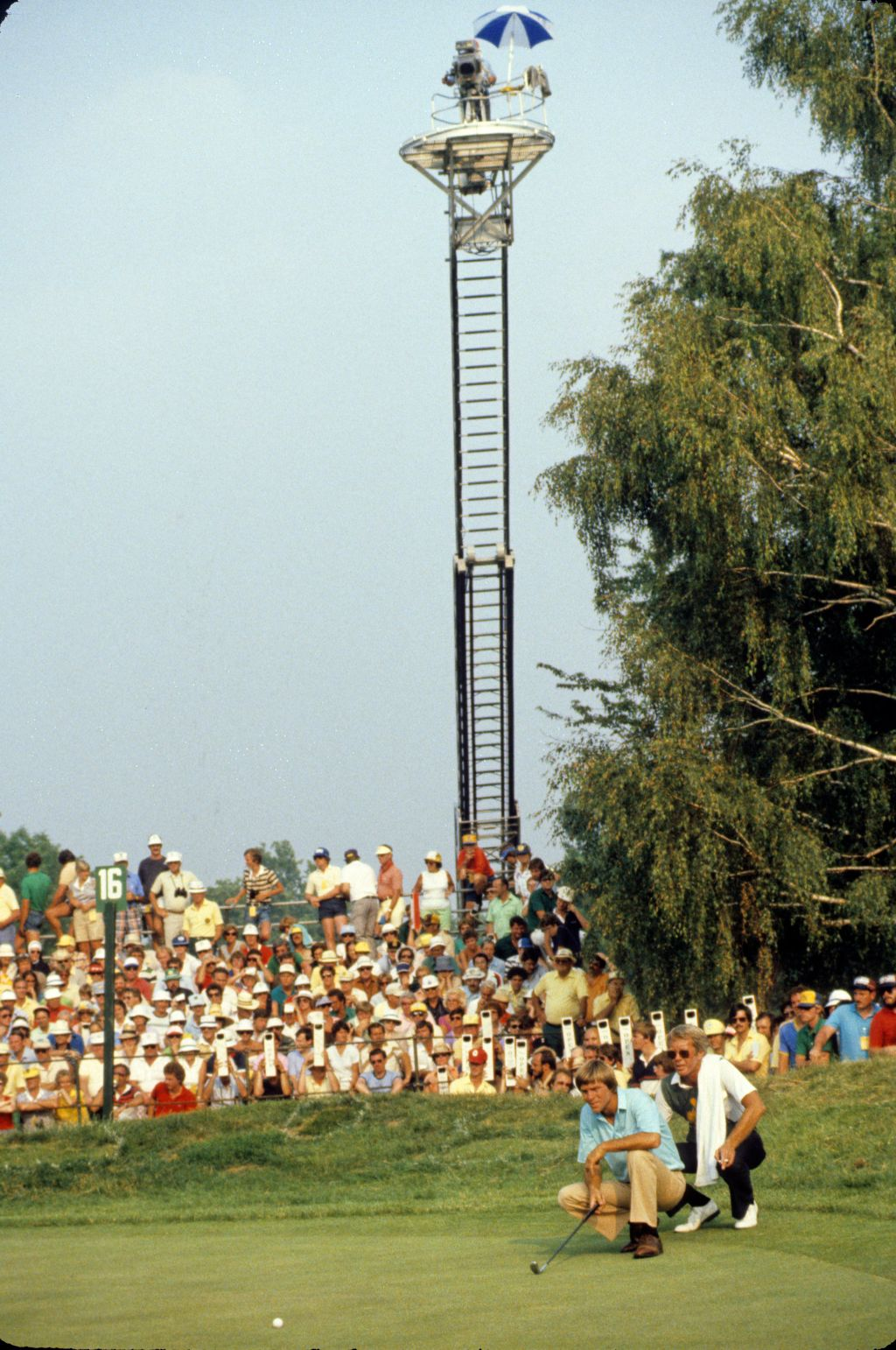 Bill Rogers and his caddie lining up a putt with a hi-rise TV tower catching the action during the 1981 US Open