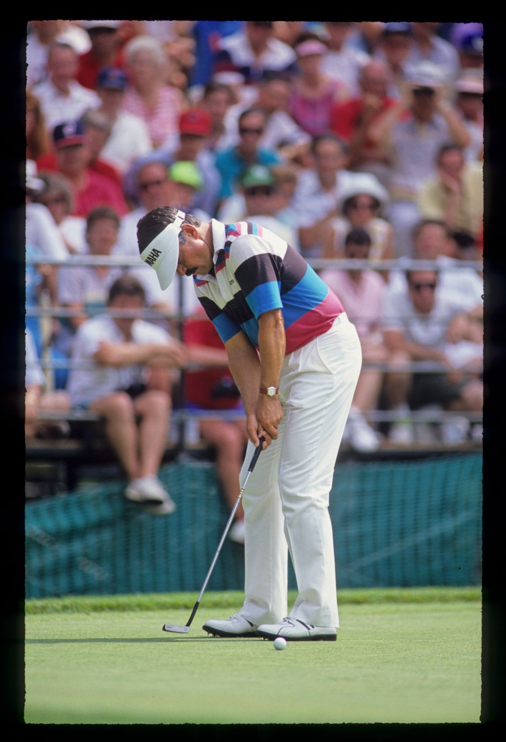 Scott Simpson sending a putt on its way in front of the gallery during the 1990 US Open