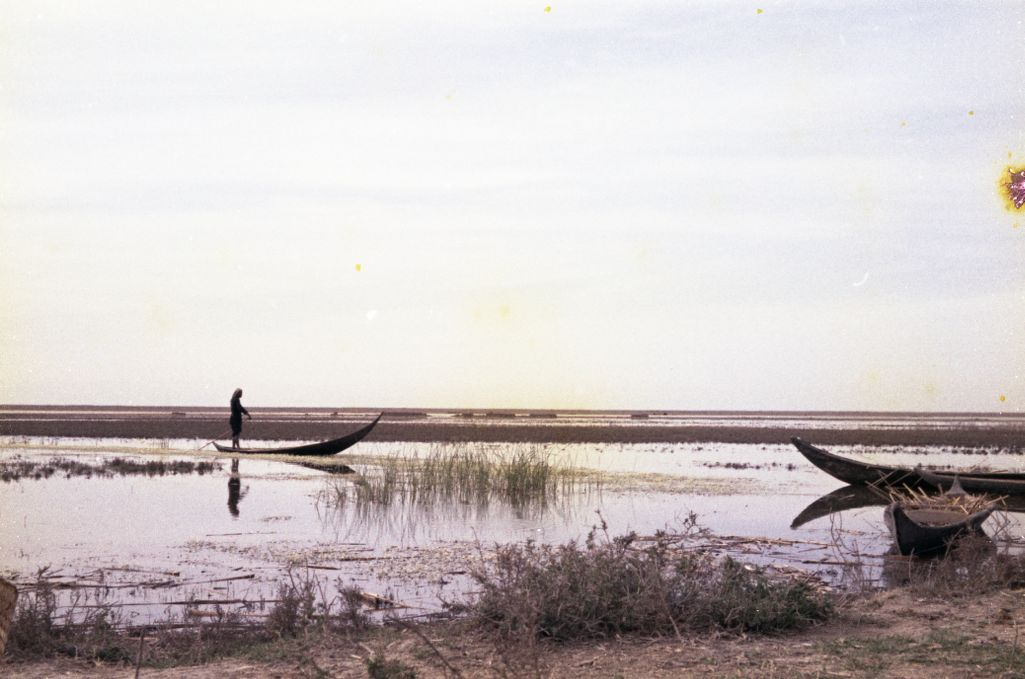 Unidentified figure on boat in the marshlands of Southern Iraq