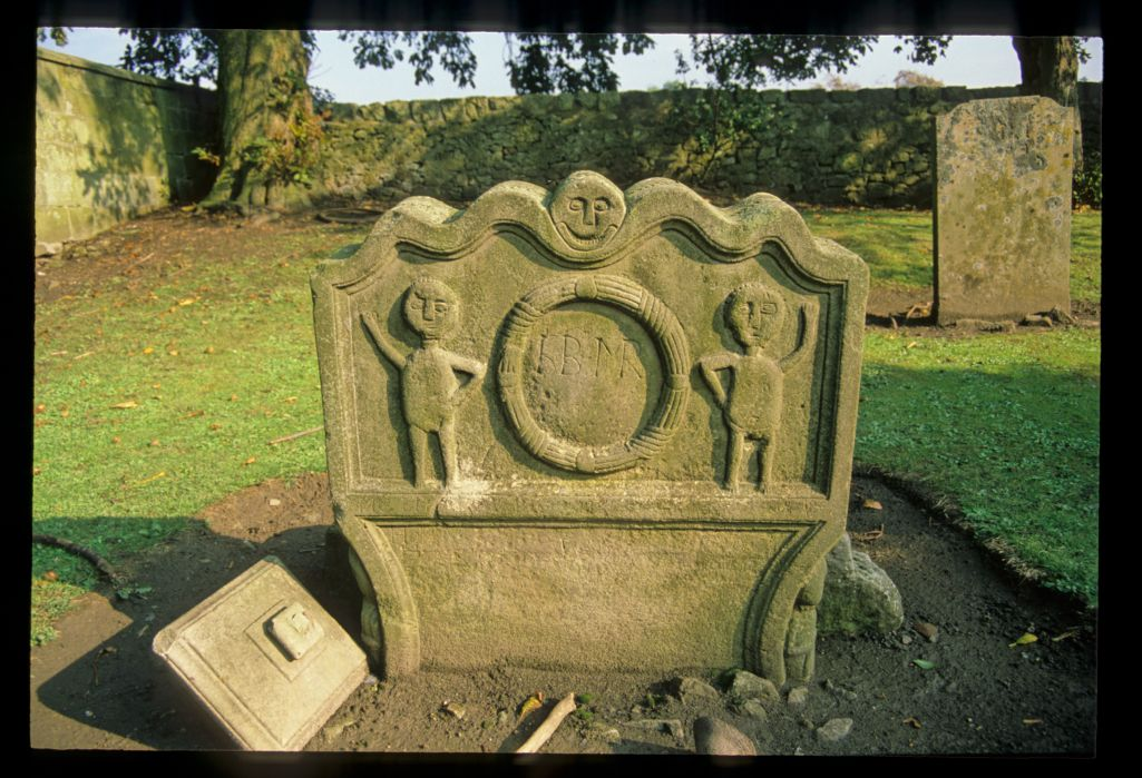 Gravestone top with two figures standing beside a wreath set below an 'imp' face, Torphichen.