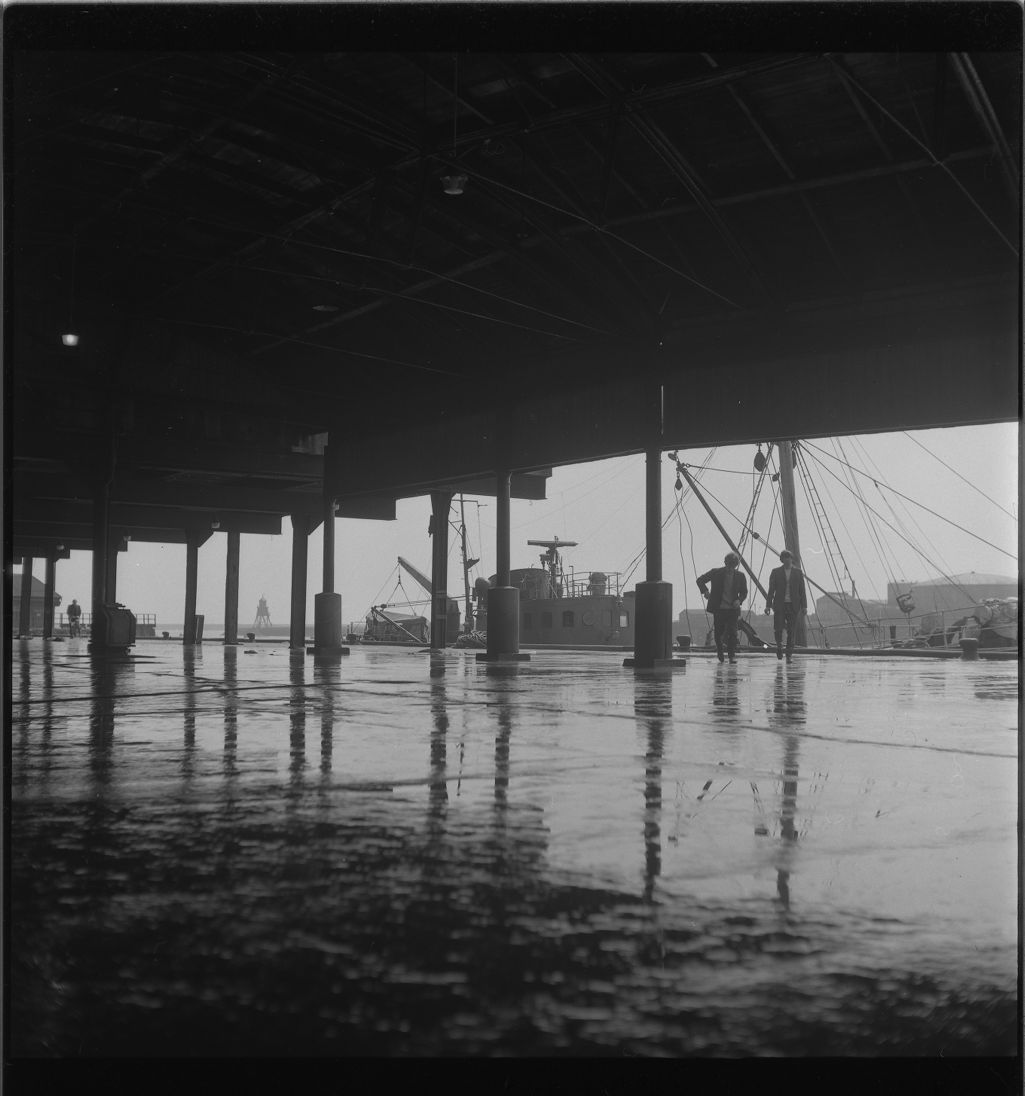 [The wet floor of the docks building with two men standing in the background, South Shields fishing docks]