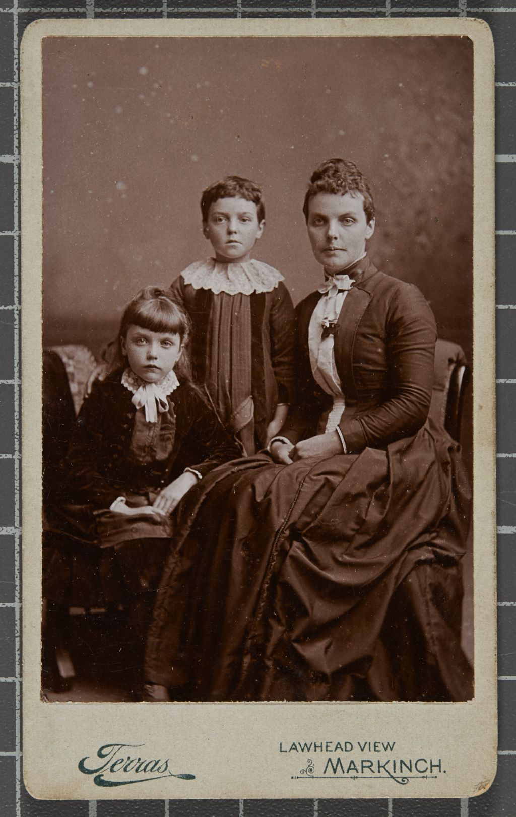 Group studio portrait of a woman and a young girl seated and a young boy standing.