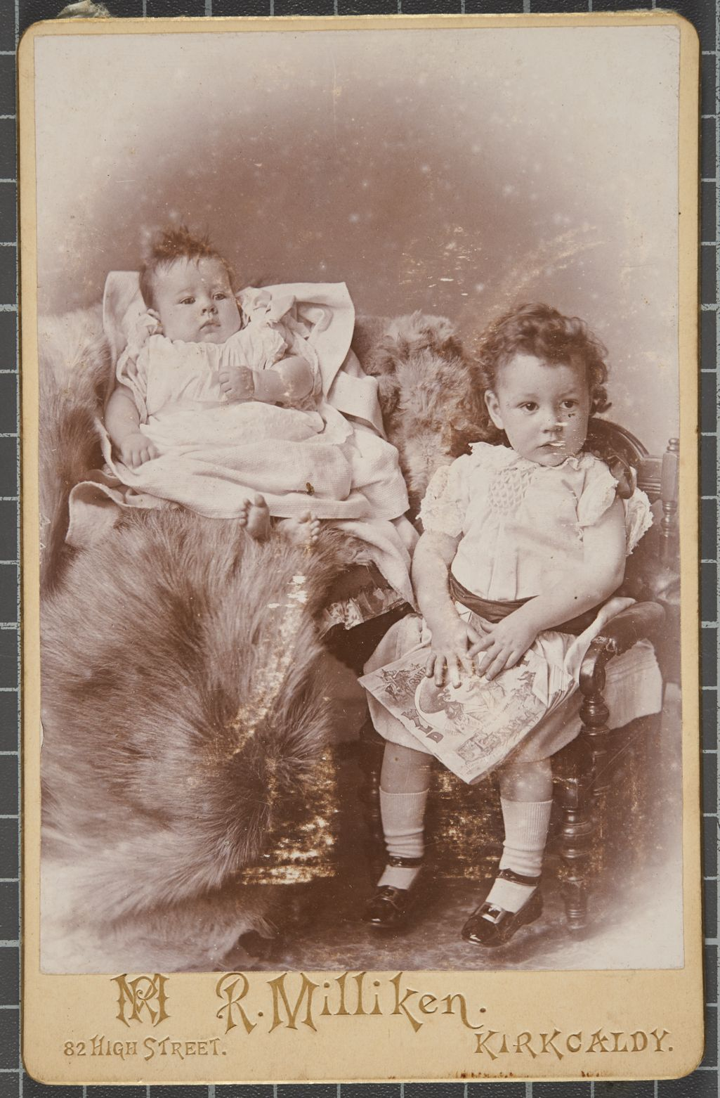 Studio portrait of a young boy seated next to another infant posed on a fur rug.