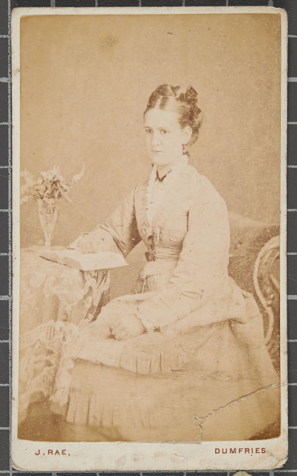 Studio portrait of a woman seated with a table and book.