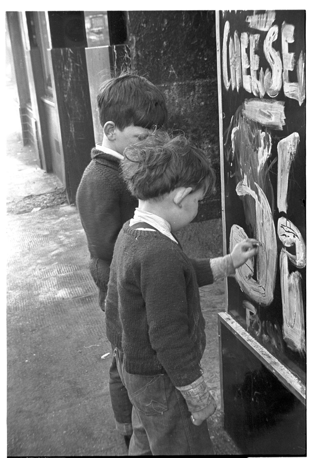 [Children Playing with Grocer's Sign]