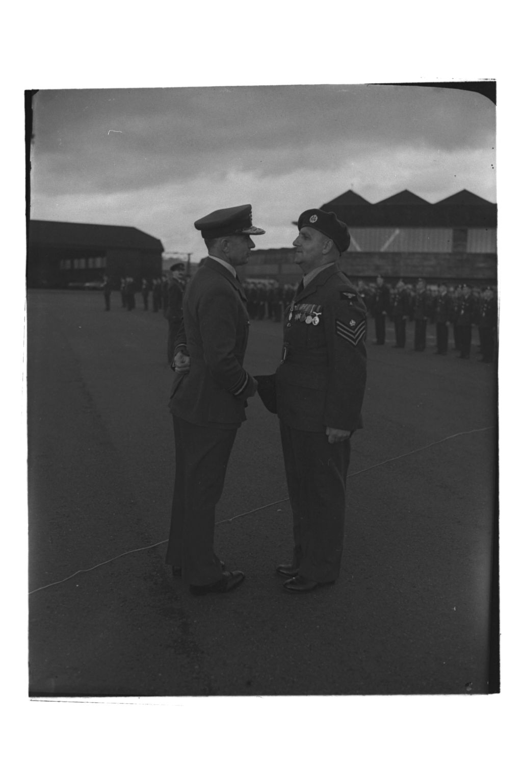 Air Chief Marshal Sir Basil Embry congratulates Flight Sergeant Henderson after presenting a British Empire Medal to him, RAF Leuchars.