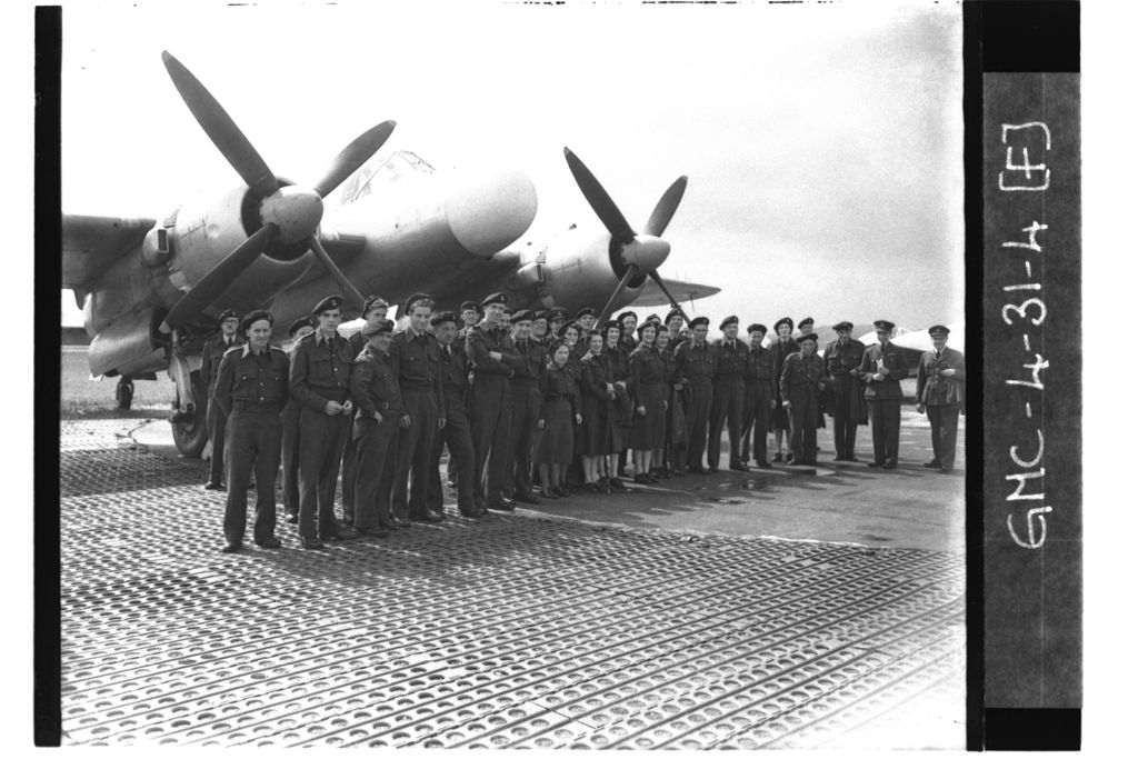 ROC (Royal Observer Corps) personnel standing on ground before Bristol Brigand plane, RAF Leuchars.