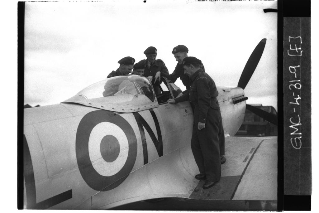 ROC (Royal Observer Corps) personnel standing on wing of Spitfire plane inspecting the cockpit, RAF Leuchars.