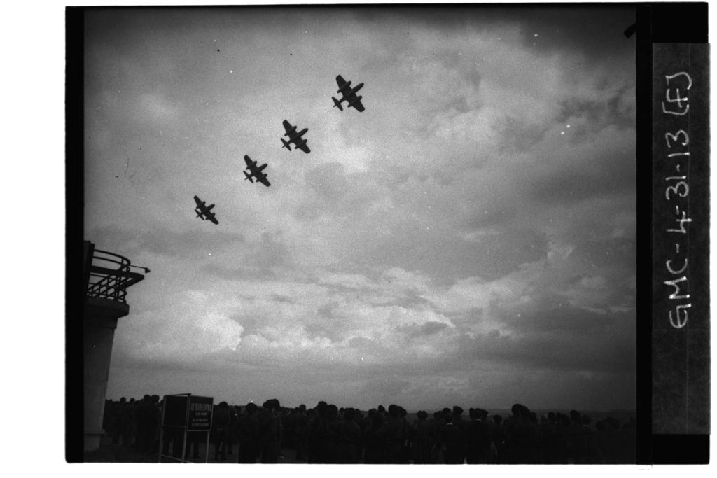 Four Gloster Meteor planes flying over ROC (Royal Observer Corps) personnel standing looking skywards, RAF Leuchars.