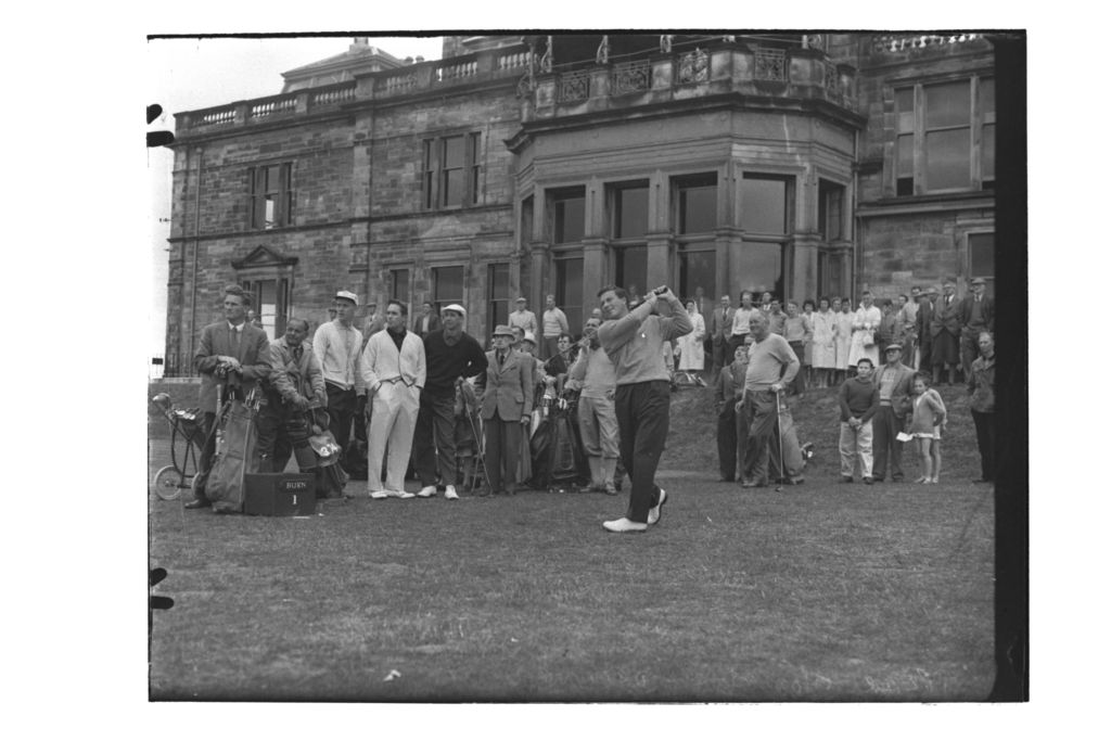 Peter Thomson tees off from the 1st Tee of the Old Course watched by Frank Stranahan and Joe Carr, the Centenary Open Championship, St Andrews.