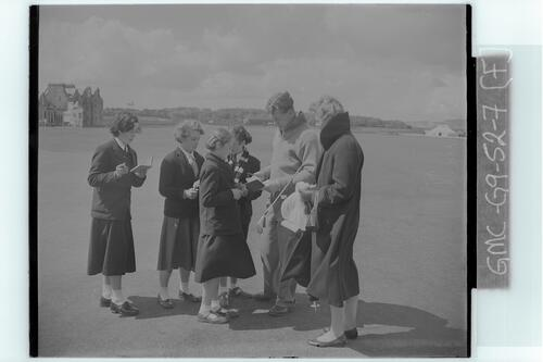 The Walker Cup Match, 1955. Ian Caldwell (GB) with autograph hunters, the Old Course, St Andrews.