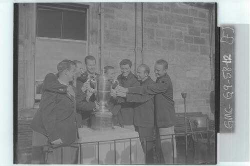 The Walker Cup Match, 1955. Members of the victorious American (USA) team, each with a hand on the trophy, St Andrews.