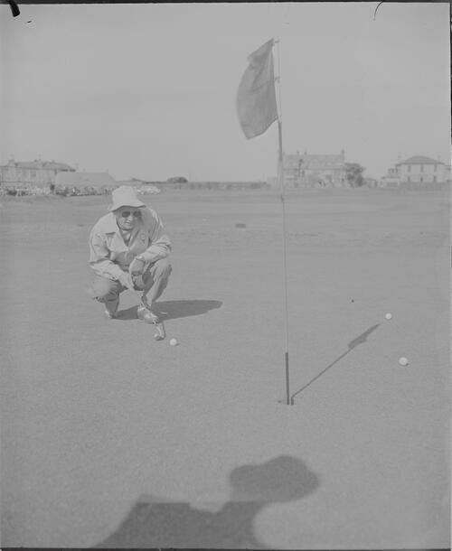 Golfer lines up his putt during the British Amateur Golf Championship, Prestwick.
