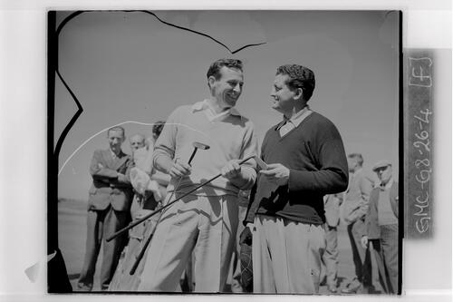 Two golfers discuss golf clubs at the British Amateur Golf Championship, Prestwick.