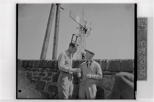 Two golfers discuss a golf club at the British Amateur Golf Championship, Prestwick.