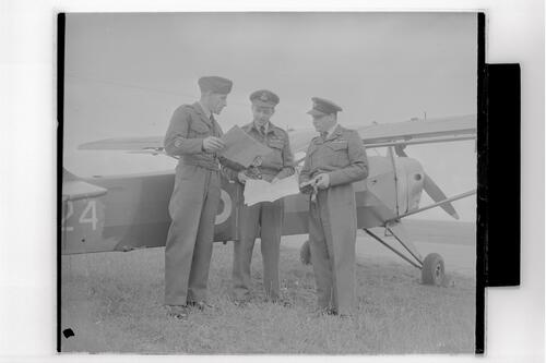 Royal Artillery (Army) and RAF officers standing beside plane reading maps, RAF Ouston.