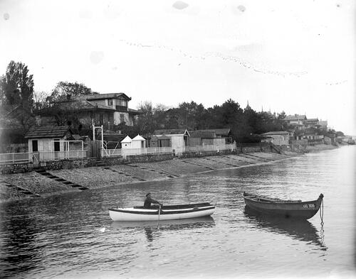 Boats by the shore with houses in the background