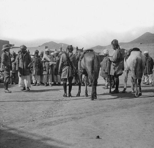 Military and local men standing before fort, India.