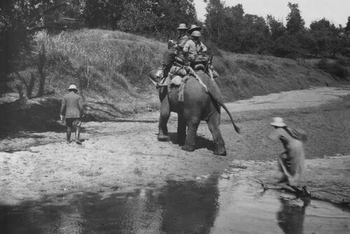 Elephant and travellers crossing river.