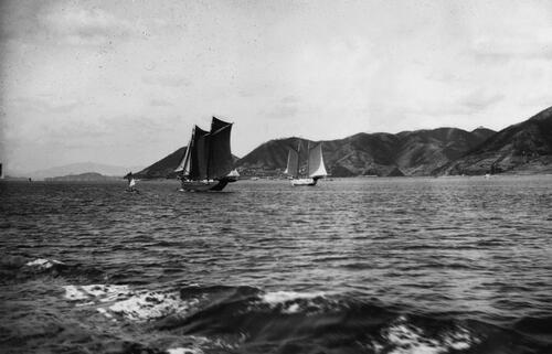 Chinese junk boats sailing past hilly coast.