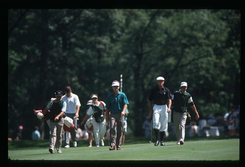 Golfers Nick Faldo, Tom Watson and Payne Stewart approach the green with their caddies at the 1990 US Open Championship at Medinah